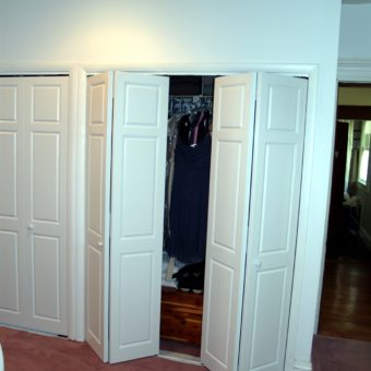 White raised panel large bi-fold open bedroom closet doors