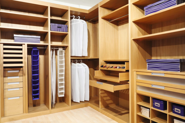 Custom walk in bedroom closet with built in accessory organizers, shelving, and hanging rods, with frosted glass drawers