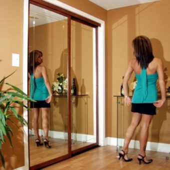 Woman looking at herself in walnut mirror sliding closet doors