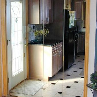 Frameless mirror bi-fold door in kitchen