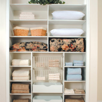 White shelving and organization units in linen closet