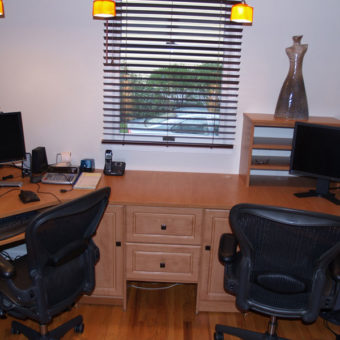 Custom dual desk with built in wall unit and organizers for small home office with black blinds window treatment