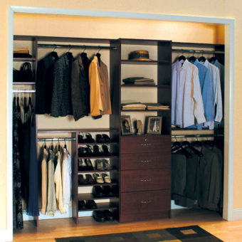 Black wall unit in custom reach-in bedroom closet with shoe organization and wardrobes
