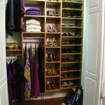Wall unit in custom reach-in bedroom closet with shoe organizers