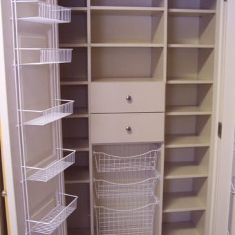 Built in unit in reach-in kitchen cupboard with pull-out organizers, shelving and drawers