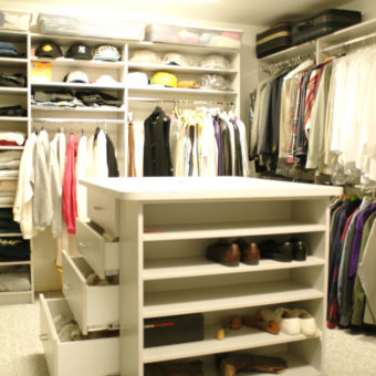 White walk in bedroom closet with built in hanging rods and shelving units and a custom island organizer