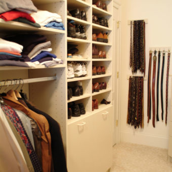 Built in wall unit with shelving for shoes and clothing with hooks for belt storage in bedroom walk in closet