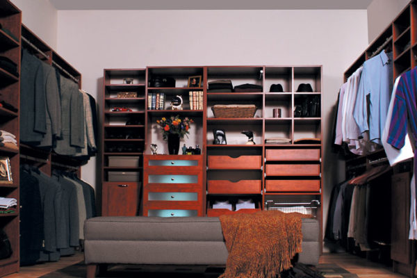 Dressing room with dark wood and custom shelving and hanging rods with drawers and seating area