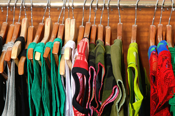 Clothing on wooden hangers in bedroom closet