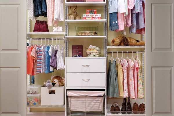 Kid's reach-in bedroom closet with built in wire shelving, hanging rods, organizing bins, hamper, and sliding doors