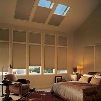 Window treatment with shades and skylight in bedroom