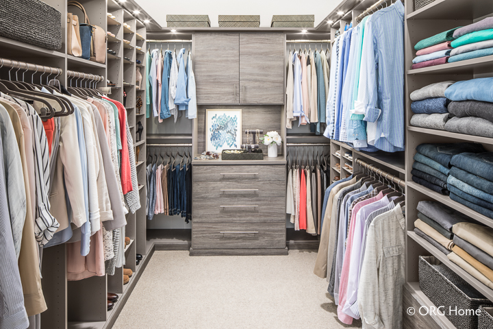 A grey colored walk in wrap around closet
