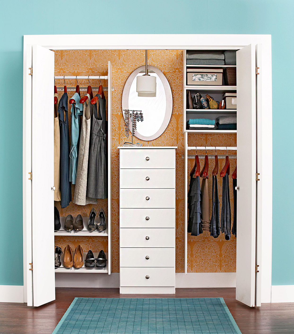 A single sided walk in closet with a dresser inside