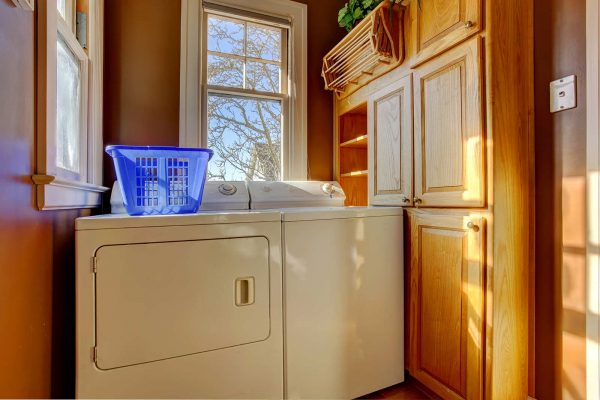 washer and dryer machine next to wood cabinets