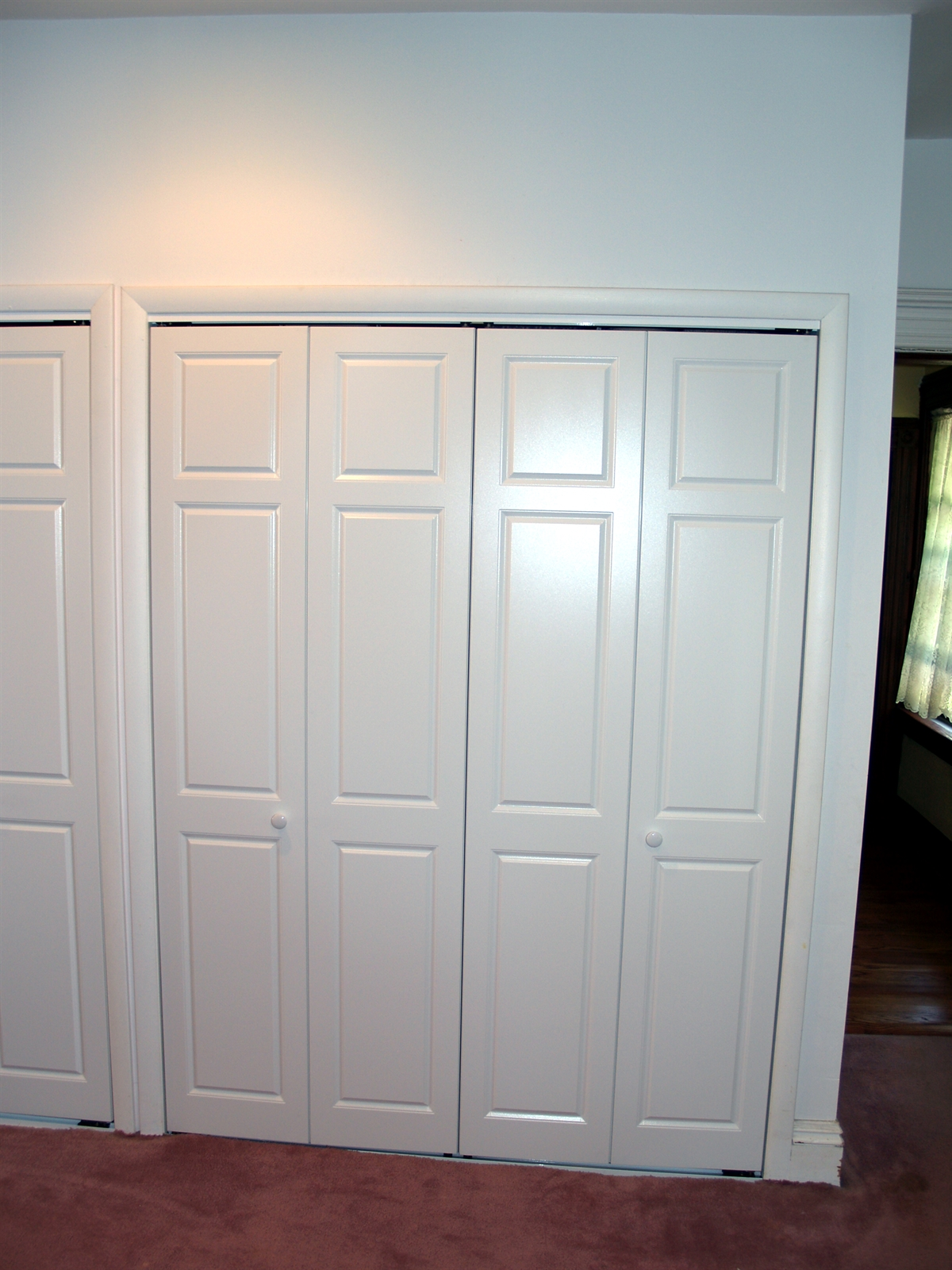 White raised panel large bi-fold bedroom closet doors