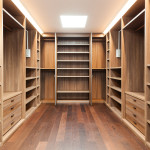 Large walk in closet with drawers, hanging rods, and custom shelving