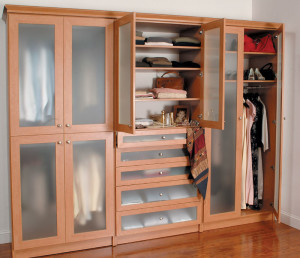 Large dual wardrobe with frosted glass doors and drawers in bedroom with opened and closed doors