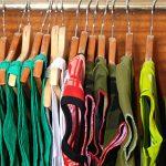 Clothing on wooden hangers in bedroom closet